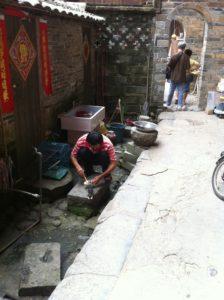 土楼の中で鳩に餌をやる中国人